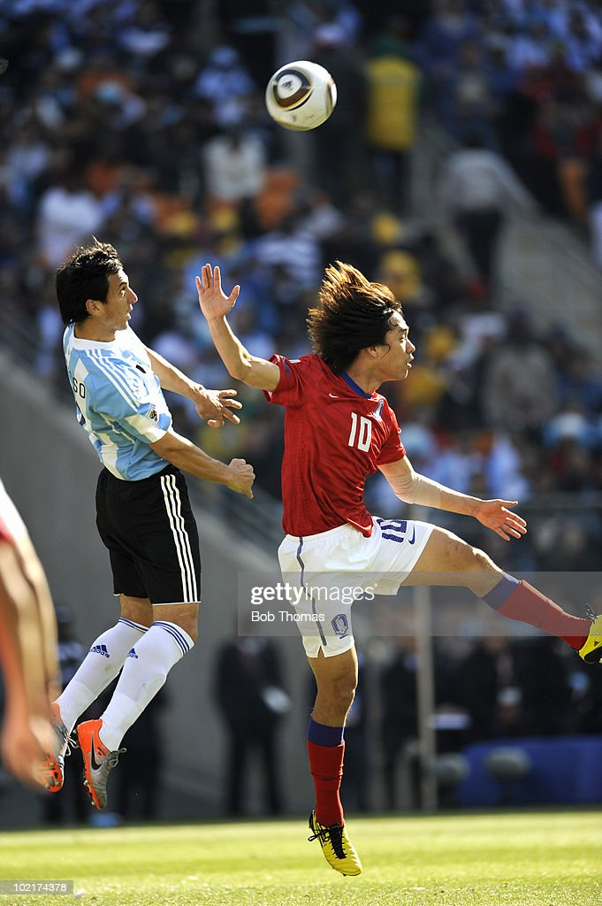 Nicolas Burdisso of Argentina heads the ball with Park ChuYoung of South Korea during the 2010 FIFA World Cup South Africa Group B match between...