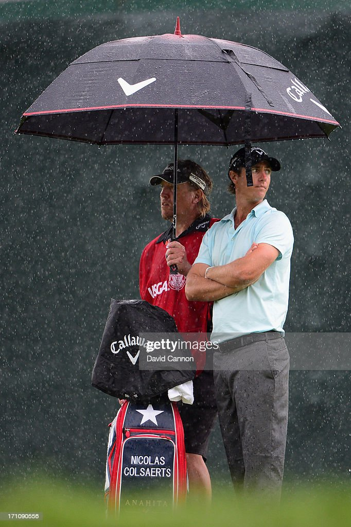 Nicolas Colsaerts of Belgium waits under an umbrella alongside his caddie during the final round of the 113th U.S. Open at Merion Golf Club on June 16, 2013 in Ardmore, Pennsylvania.