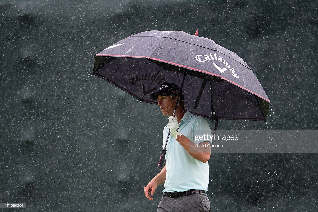 Nicolas Colsaerts of Belgium walks under an umbrella during the final round of the 113th U.S. Open at Merion Golf Club on June 16, 2013 in Ardmore, Pennsylvania.