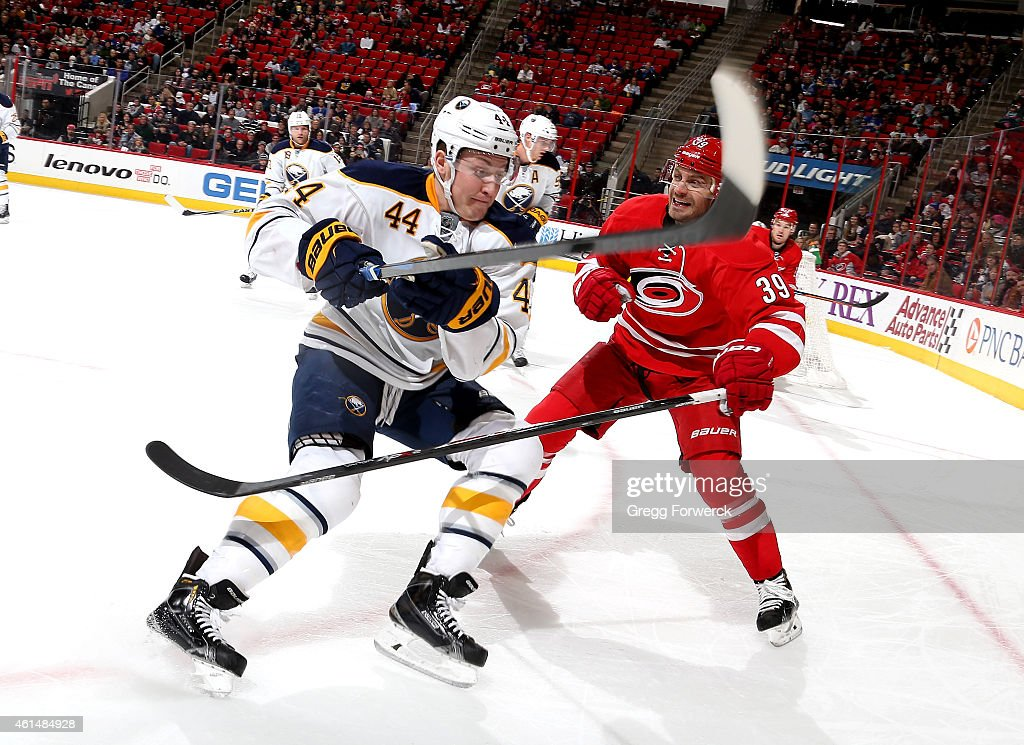 Nicolas Deslauriers #44 of the Buffalo Sabres battles in the corner with Patrick Dwyer #39 during their NHL game at PNC Arena on January 8, 2015 in Raleigh, North Carolina.
