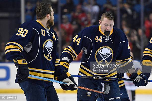 Nicolas Deslauriers of the Buffalo Sabres holds a puck in his mouth during warmups before the game against the Chicago Blackhawks at the First...