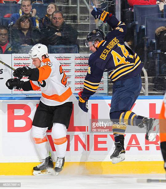 Nicolas Deslauriers of the Buffalo Sabres jumps to avoid a check from Ryan White of the Philadelphia Flyers on February 15 2015 at the First Niagara...