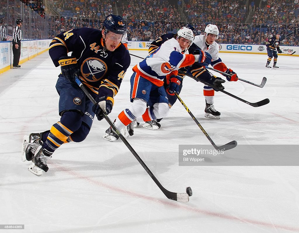 Nicolas Deslauriers #44 of the Buffalo Sabres skates the puck around Ryan Strome #18 and Brock Nelson #29 of the New York Islanders on April 13, 2014 at the First Niagara Center in Buffalo, New York.