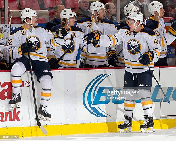 Nicolas Deslauriers of the Buffalo Sabres taps gloves with teammates on the bench after scoring a goal during a NHL game against the Detroit Red...