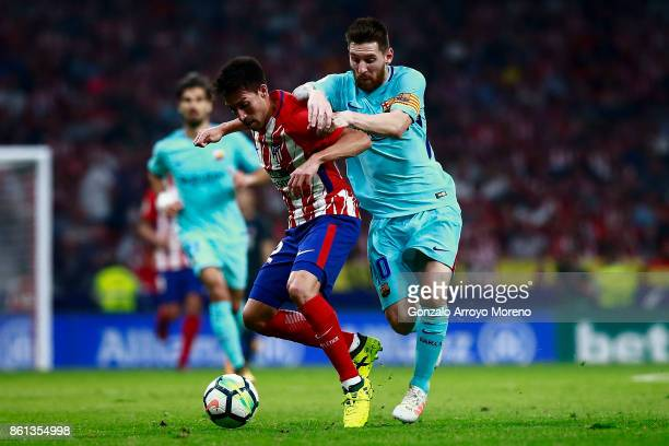 Nicolas Gaitan of Atletico de Madrid competes for the ball with Lionel Messi of FC Barcelona during the La Liga match between Club Atletico Madrid...