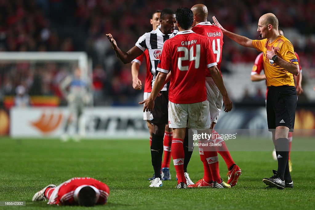 Nicolas Gaitan (R) of Benfica lies on the pitch as Shola Ameobi of Newcastle United is accused of using his arm by Luisao (#4) and is subsequently shown a yellow card by referee Antony Gautier (R), during the UEFA Europa League Quarter- Final First Leg match between Benfica and Newcastle United at the Estadio da Luz on April 4, 2013 in Lisbon, Portugal.