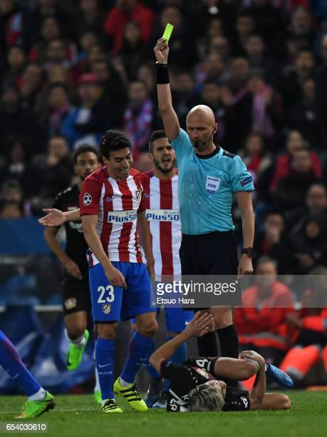 Nicolas Gaitan of Club Atletico de Madrid is shown an yellow card by referee Sergei Karasev during the UEFA Champions League Round of 16 second leg...