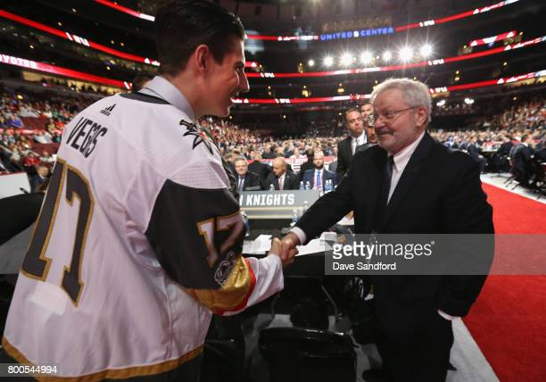 Nicolas Hague 34th overall pick of the Vegas Golden Knights shakes the hand of a Golden Knights draft team member during the 2017 NHL Draft at United...