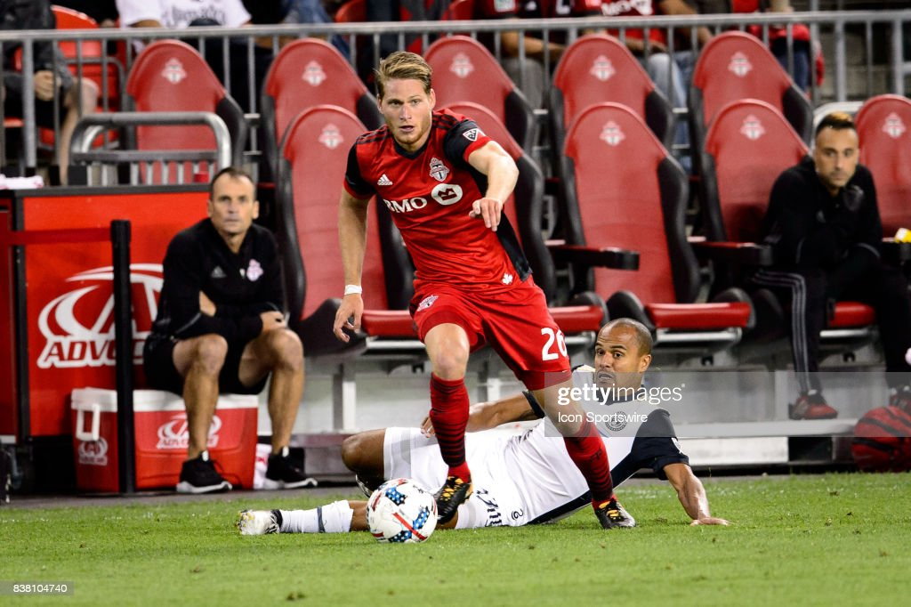 Nicolas Hasler (26) of Toronto FC avoids a tackle from Fabinho (33) of Philadelphia Union during the second half of the MLS Soccer regular season game between Toronto FC and Philadelphia Union on August 23, 2017, at BMO Field in Toronto, ON, Canada.