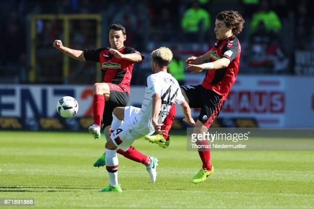 Nicolas Hoefler and Caglar Soeyuencue of Freiburg fight for the ball with Kevin Kampl of Leverkusen during the Bundesliga match between SC Freiburg...