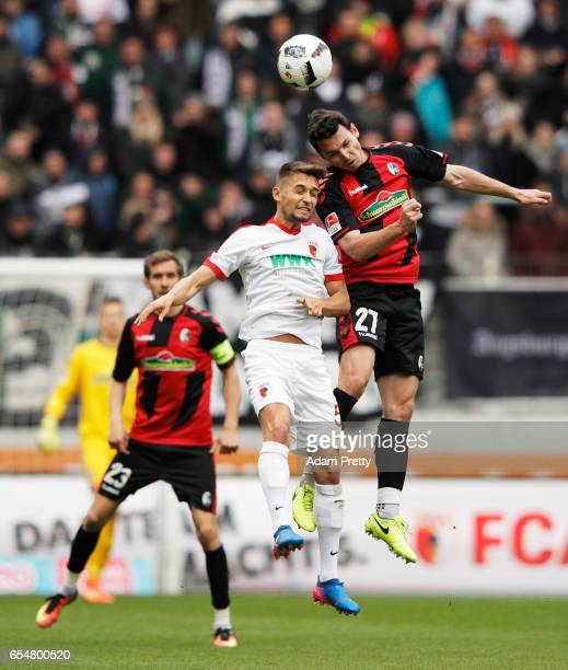 Nicolas Hoefler of Freiburg is challenged by Moritz Leitner of Augsburg during the Bundesliga match between FC Augsburg and SC Freiburg at WWK Arena...