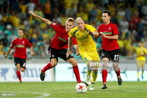Nicolas Hofler and Philip Lienhart of SC Freiburg and Senijad Ibrecic of NK Domzale battle for the ball during the UEFA Europa League Third...