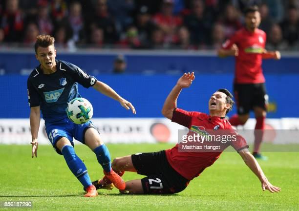 Nicolas Hofler of SC Freiburg is challenged by Bartosz Kapustka of SC Freiburg during the Bundesliga match between SportClub Freiburg and TSG 1899...