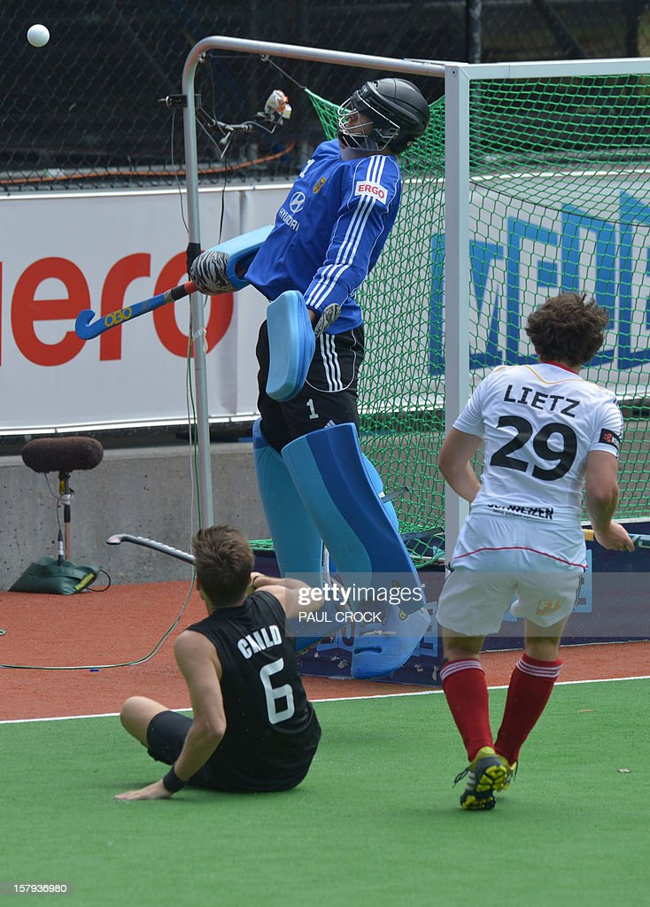 Nicolas Jacobi of Germany (C) uses his chest pad to deflect the ball from goal during the match against New Zealand at the men's Hockey Champions Trophy tournament in Melbourne on December 8, 2012. IMAGE STRICTLY RESTRICTED TO EDITORIAL USE - STRICTLY NO COMMERCIAL USE AFP PHOTO/Paul CROCK