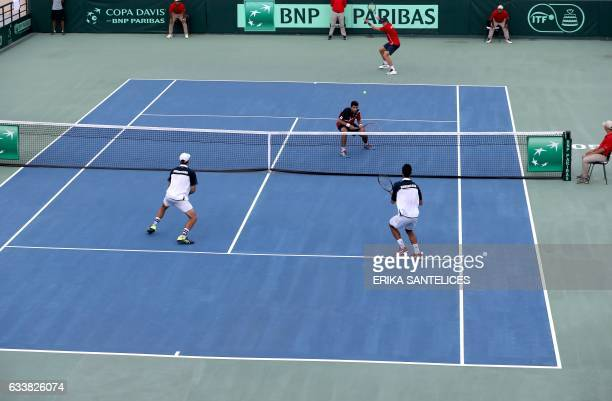 Nicolas Jarry of Chile returns to the ball next to teammate Hans Podlipnik during the Davis Cup first round double tennis match against Dominican...