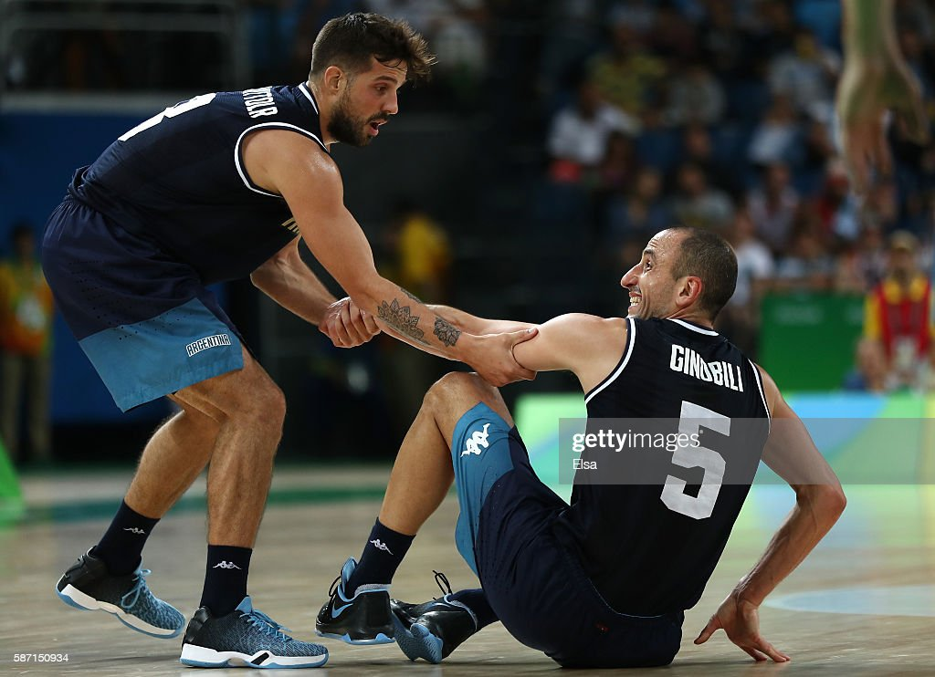 Nicolas Laprovittola of Argentina helps up teammate Manu Ginobili during a Men's preliminary round basketball game between Nigeria and Argentina on...
