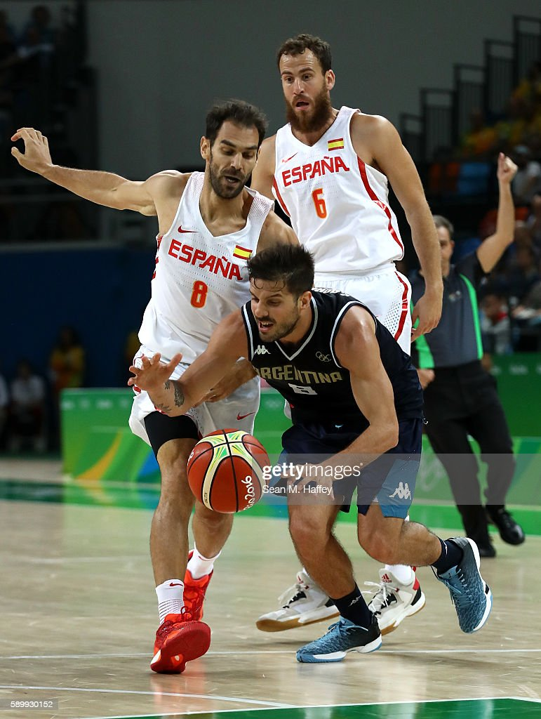 Nicolas Laprovittola of Argentina moves the ball against Jose Calderon of Spain and Sergio Rodriguez of Spain during a Men's Basketball Preliminary...
