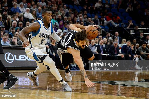 Nicolas Laprovittola of the San Antonio Spurs trips while driving to the basket against Kris Dunn of the Minnesota Timberwolves during the game on...