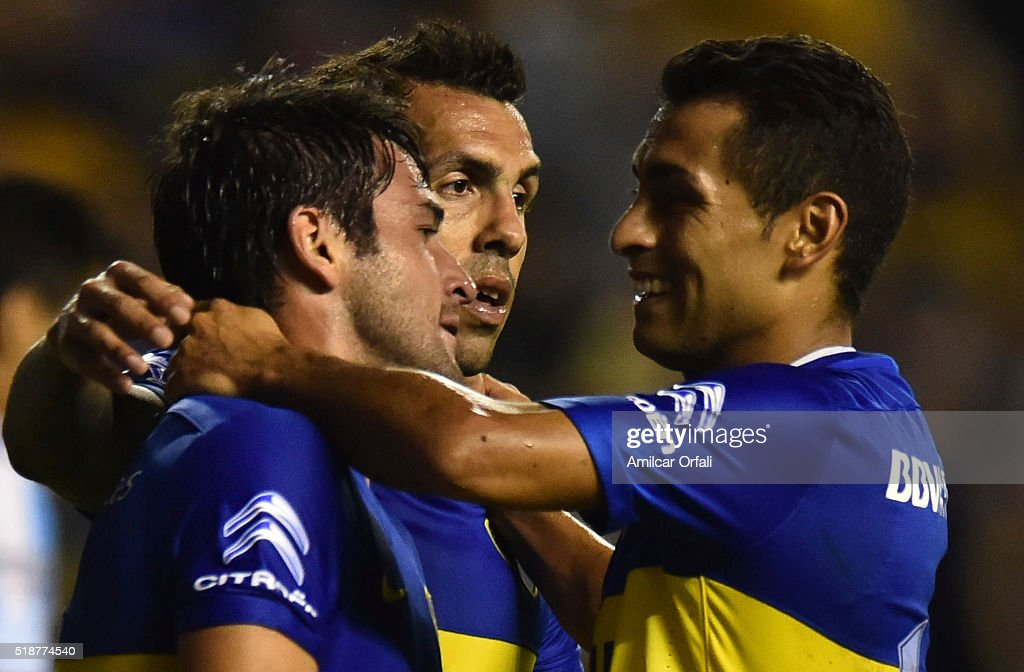 Nicolas Lodeiro of Boca Juniors celebrates with teammate Federico Carrizo and Carlos Tevez after scoring the third goal his team during a match...