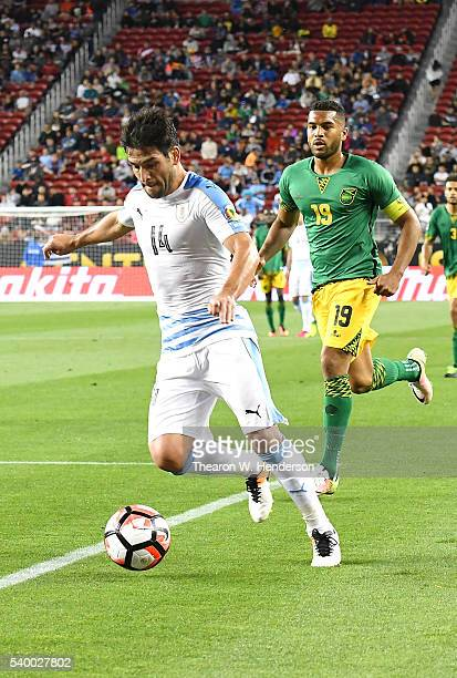 Nicolas Lodeiro of Uruguay dribbles the ball away fron Adrian Mariappa of Jamaica during the 2016 Copa America Centenario Group match play between...