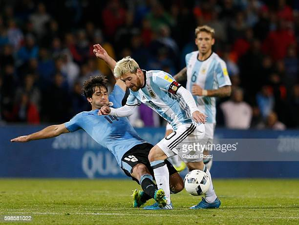 Nicolas Lodeiro of Uruguay slides to defend against Lionel Messi of Argentina during a match between Argentina and Uruguay as part of FIFA 2018 World...