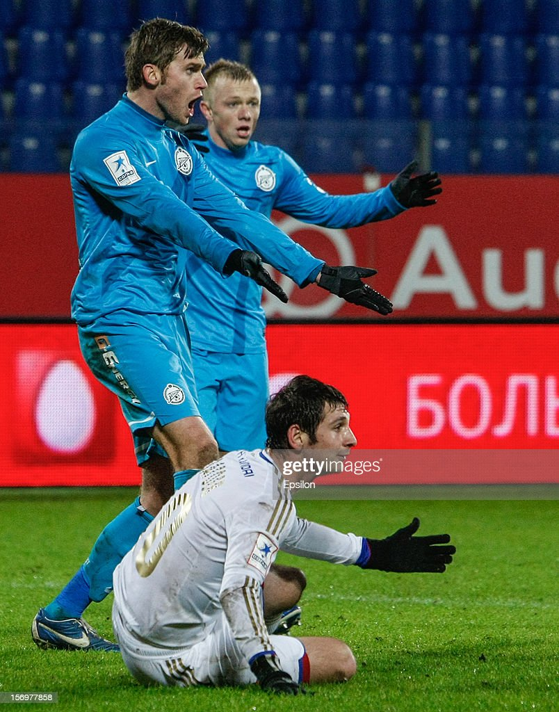 Nicolas Lombaerts (L) and Renat Yanbaev of FC Zenit St. Petersburg and <a gi-track='captionPersonalityLinkClicked' href=/galleries/search?phrase=Alan+Dzagoev&family=editorial&specificpeople=5436464 ng-click='$event.stopPropagation()'>Alan Dzagoev</a> of PFC CSKA Moscow (bottom) react during the Russian Football League Championship match between FC Zenit St. Petersburg and PFC CSKA Moscow at the Petrovsky Stadium on November 26, 2012 in St. Petersburg, Russia.