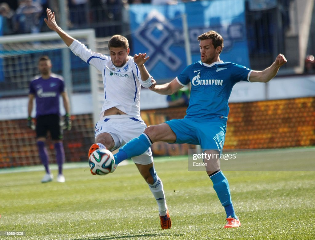 <a gi-track='captionPersonalityLinkClicked' href=/galleries/search?phrase=Nicolas+Lombaerts&family=editorial&specificpeople=4332055 ng-click='$event.stopPropagation()'>Nicolas Lombaerts</a> of FC Zenit St. Petersburg (R) and Artyom Danilenko of FC Volga Nizhny Novgorod vie for the ball during the Russian Football League Championship match between FC Zenit St. Petersburg and FC Volga Nizhny Novgorod at the Petrovsky stadium on April 26, 2014 in St. Petersburg, Russia.