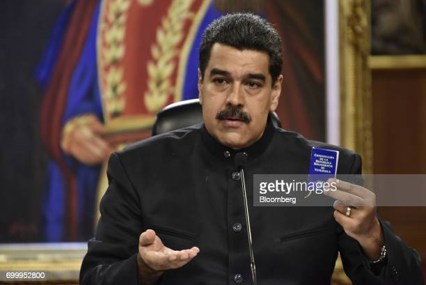 Nicolas Maduro president of Venezuela holds up a copy of the Venezuelan constitution during a press conference in Caracas Venezuela on Thursday June...