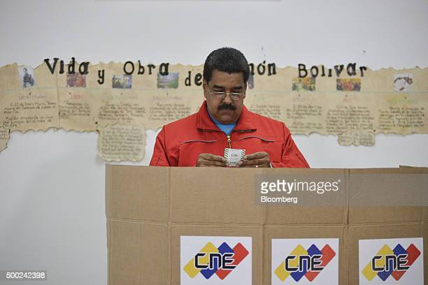 Nicolas Maduro Venezuela's president reviews his ballot slip in a polling booth during the national congressional elections in Caracas Venezuela on...
