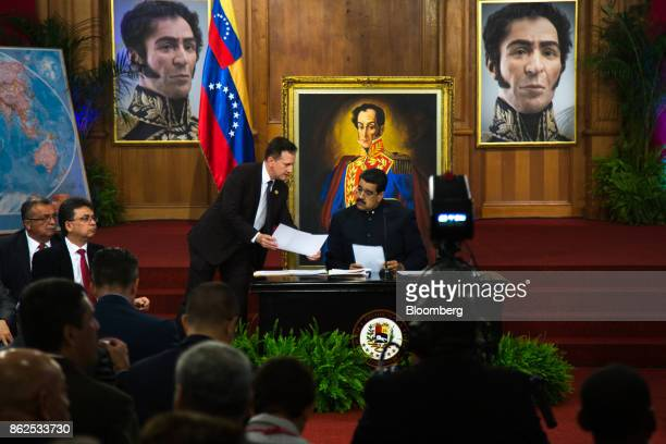 Nicolas Maduro Venezuela's president right receives paperwork during a press conference at the Miraflores Palace in Caracas Venezuela on Tuesday Oct...