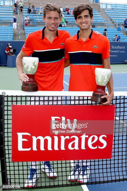 Nicolas Mahut and PierreHughes Herbert of France pose with the winner's trophy after defeating Jamie Murray of Great Britain and Bruno Soares of...