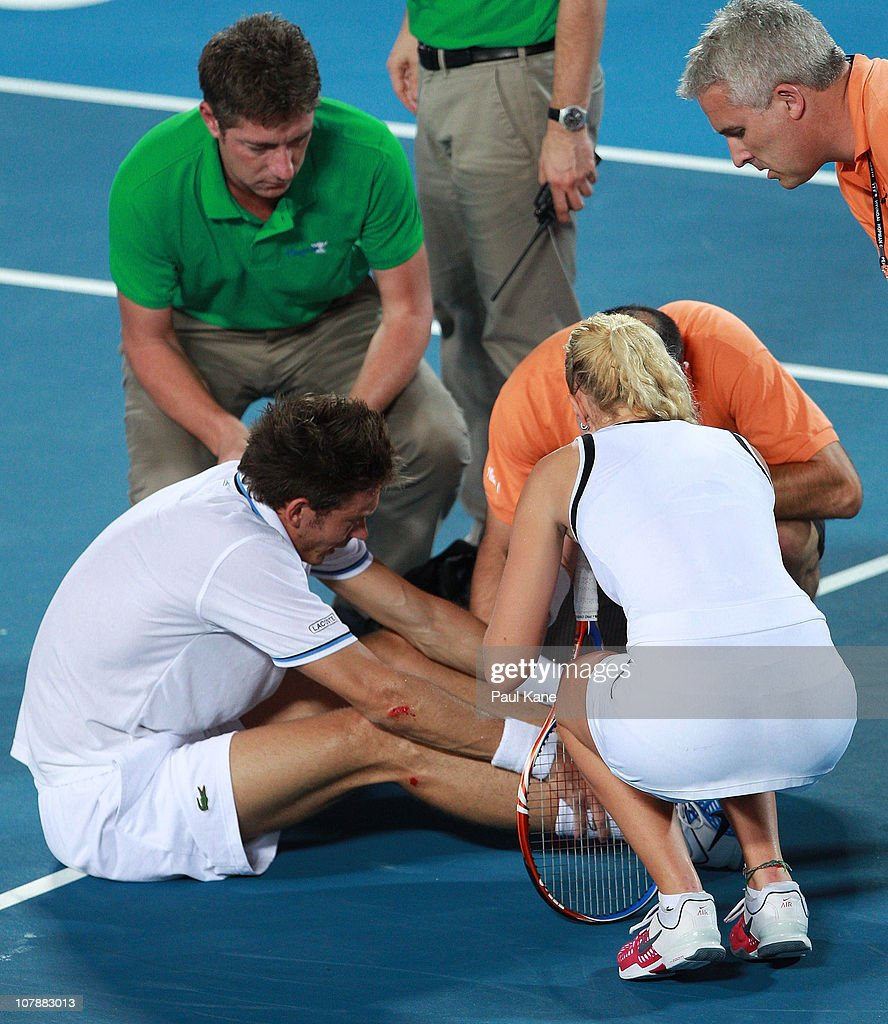 <a gi-track='captionPersonalityLinkClicked' href=/galleries/search?phrase=Nicolas+Mahut&family=editorial&specificpeople=547869 ng-click='$event.stopPropagation()'>Nicolas Mahut</a> of France receives medical attention on the court injuring his ankle during his mixed doubles match partnered with <a gi-track='captionPersonalityLinkClicked' href=/galleries/search?phrase=Kristina+Mladenovic&family=editorial&specificpeople=4835181 ng-click='$event.stopPropagation()'>Kristina Mladenovic</a>, against Andy Murray and Laura Robson of Great Britain on day five of the Hopman Cup on January 5, 2011 in Perth, Australia.