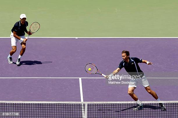 Nicolas Mahut of France returns a shot to Mike Bryan and Bob Bryan while playing with PierreHugues Herbert of France during the Miami Open presented...