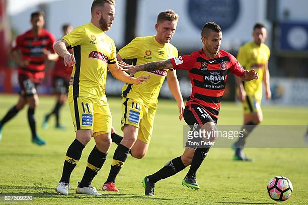 Nicolas Martinez of the Wanderers contests the ball with Adam Berry and Connor Pain of the Mariners during the round nine ALeague match between...