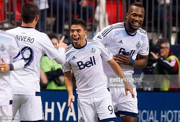 Nicolas Mezquida of the Vancouver Whitecaps FC celebrates with Octavio Rivero and Kendall Waston after scoring a goal against the Portland Timbers in...