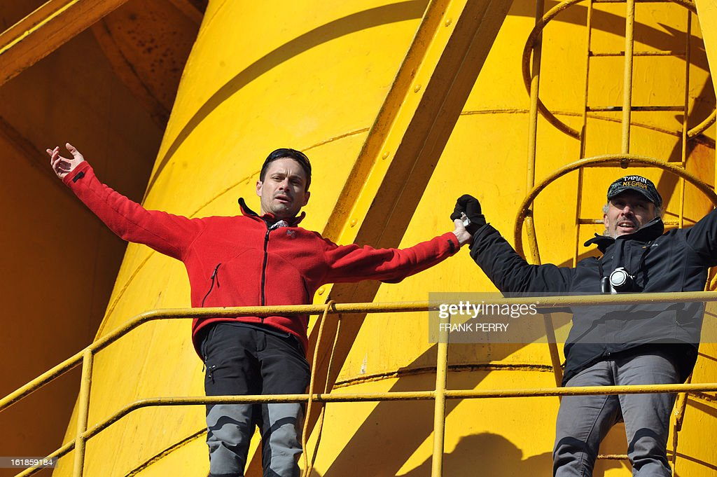 Nicolas Moreno (L) gestures after climbing a 43-meter crane on February 17, 2013 in Nantes, to join Serge Charnay (R) on the third day of a protest for his rights as a father. Another man on February 16 climbed another crane in 'an act of solidarity' with Charnay, an action sanctioned by French association 'SOS Papa' indicating that the two men are' victims of family justice in France'.