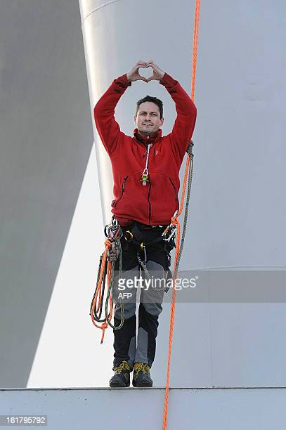 Nicolas Moreno with a teat clinging to his neck makes a heartshaped sign with his hands as he comes down from a giant crane on February 16 2013 in...