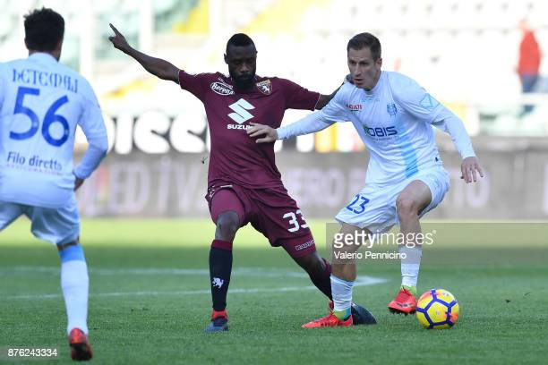 Nicolas N koulou of Torino FC is challenged by Valter Birsa of AC Chievo Verona during the Serie A match between Torino FC and AC Chievo Verona at...