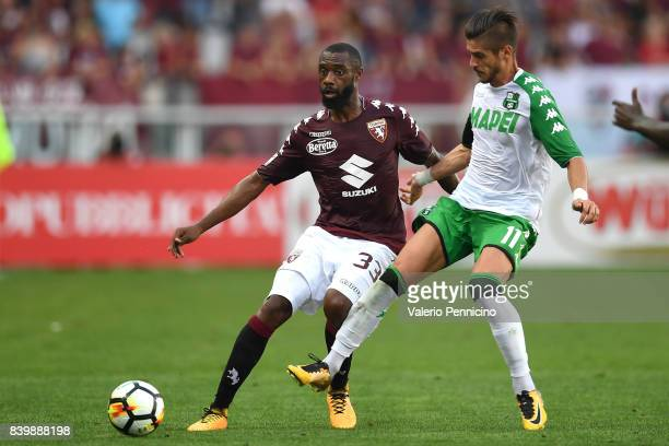 Nicolas Nkoulou of Torino FC is challenged by Diego Falcinelli of US Sassuolo during the Serie A match between Torino FC and US Sassuolo FC at Stadio...