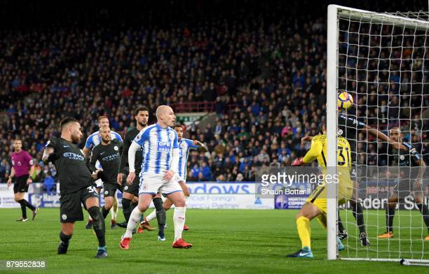 Nicolas Otamendi of Manchester City scores the first own goal as Aaron Mooy of Huddersfield Town look on during the Premier League match between...