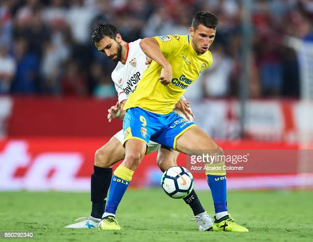 Nicolas Pareja of Sevilla FC competes for the ball with Jonathan Calleri of Union Deportiva Las Palmas during the La Liga match between Sevilla and...