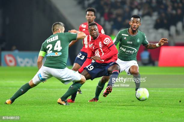 Nicolas Pepe of Lille slips between Loic Perrin of St Etienne and Habib Maiga of St Etienne during the Ligue 1 match between Lille OSC and AS...