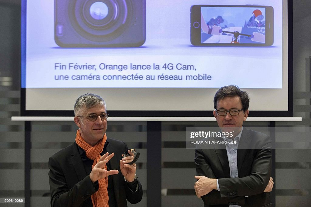 Nicolas Roy (R), CTO for networks and services at French telecommunications corporation Orange, and Olivier Faure, director of Orange's East Center, present a new connected camera during a press conference at Orange's mobile phone supervision center in Lyon on February 10, 2016. / AFP / ROMAIN LAFABREGUE