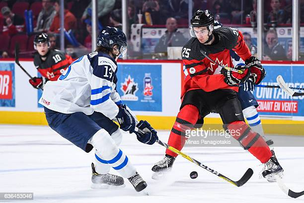 Nicolas Roy of Team Canada plays the puck in front of Henrik Borgstrom of Team Finland during the IIHF exhibition game at the Bell Centre on December...