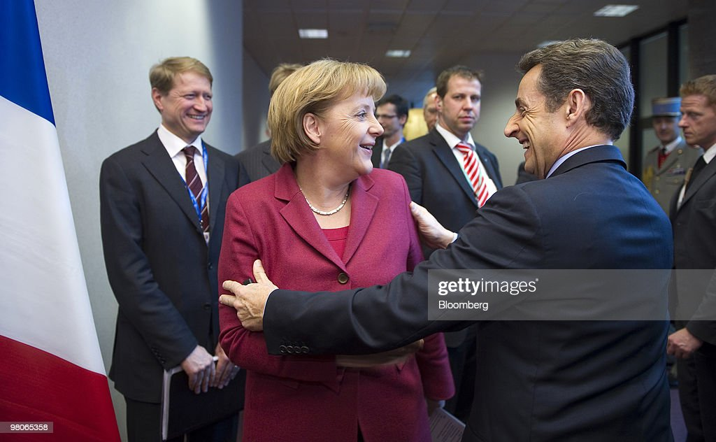 Nicolas Sarkozy, France's president, right, greets Angela Merkel, Germany's chancellor, as they move between their press conferences following the European Union Summit in Brussels, Belgium, on Friday, March 26, 2010. Sarkozy capped a week of reversals with his acceptance of German demands on a contingency plan to aid Greece. Photographer: Jock Fistick/ Bloomberg