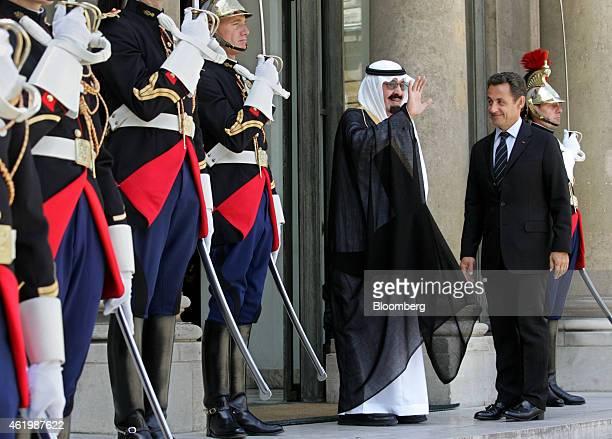 Nicolas Sarkozy France's president right looks on as Saudi Arabia's King Abdullah bin Abdulaziz Al Saud center waves to journalists from the steps of...