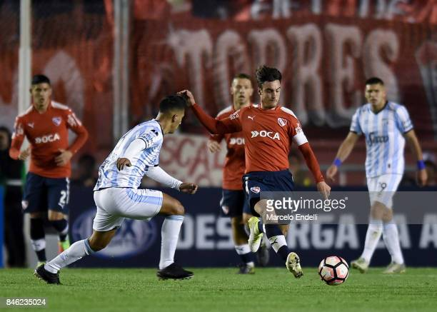 Nicolas Tagliafico of Independiente fights for the ball with Rodrigo Aliendro of Atletico Tucuman during a second leg match between Independiente and...