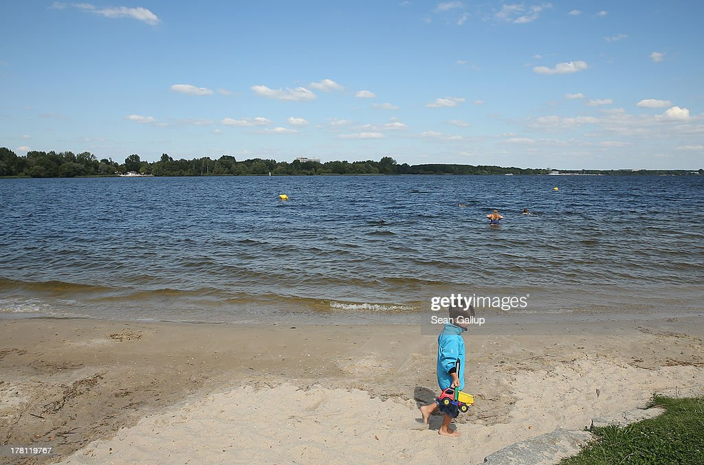 Nicolas, 4, walks along a beach on the shore of artificial Senftenberger See lake on August 26, 2013 in Niemtsch, Germany. Senftenberger See was once an open-pit lignite coal mine flooded after it shuttered in the late 1960s, and today it is popular among tourists, wind surfers and fishermen. In a development project initiated by state government, other nearby former open-pit mines that once evoked a lunar landscape are being turned into lakes in a long-term rejuvenation effort that is also intended to make the area a viable tourist destination. Mineral residue in the mines, however, is proving a difficult stumbling block that is making many of the new lakes too acidic to sustain marine life in the short term.