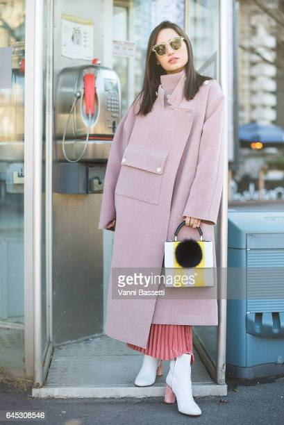 Nicole Andersson poses wearing a Ports coat and Acne boots before the Jil Sander show during Milan Fashion Week Fall/Winter 2017/18 on February 25...