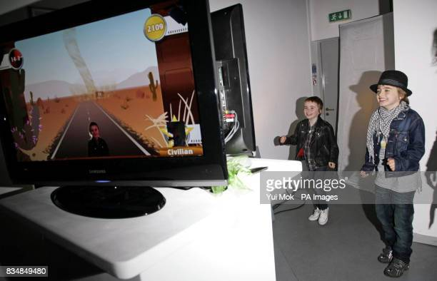 Nicole Appleton's son Gene and stepson Lennon try out the Xbox video game 'You're in the Movies' during the launch of the Xbox 360 Gaming Zone at...